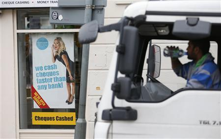 A lorry driver drinks water as he passes by a payday lending shop in London March 6, 2013. Britain's consumer watchdog has given Britain's biggest 50 payday lenders 12 weeks to change their business practices or risk losing their licenses, after finding evidence of widespread irresponsible lending. REUTERS/Suzanne Plunkett