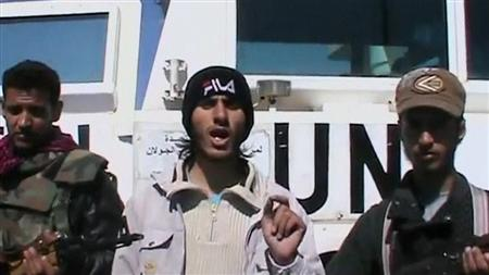 A member of the Al Yarmouk Martyr brigade makes a statement in front of a white vehicle with 'UN' written on it at what said to be Jamla, Syria near Golan Heights on March 6, 2013 in this still image taken from video posted on social media website. Syrian rebels have seized a convoy of U.N. peacekeepers near the Golan Heights and say they will hold them captive until President Bashar al-Assad's forces pull back from a rebel-held village which has seen heavy recent fighting. The capture was announced in rebel videos posted on the Internet and confirmed on Wednesday by the United Nations in New York, which said about 20 peacekeepers had been detained. REUTERS/Social Media Website via Reuters TV