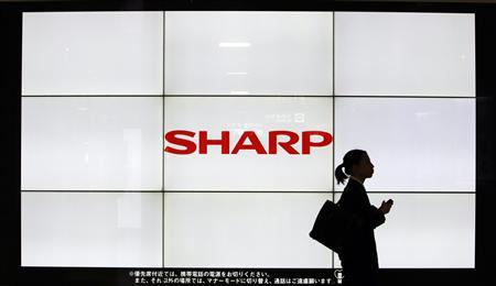 A woman walks past the Sharp Corp's Logo at a train station in Tokyo March 6, 2013. Samsung Electronics Co is set to invest $110 million in Sharp Corp , ensuring it a stable supply of TV panels and bolstering the survival chances of the Japanese maker of Apple Inc iPhone and iPad screens. REUTERS/Yuya Shino