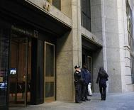 A New York City Police officer stands beside a security officer at the entrance of a Deutsche Bank office in New York's financial district December 8, 2011. REUTERS/Brendan McDermid