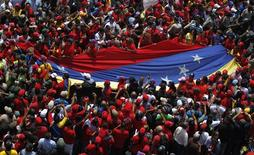 Supporters of Venezuela's late President Hugo Chavez unfurl a large national flag as they gather to see his coffin driven through the streets of Caracas, March 6, 2013. REUTERS/Jorge Dan Lopez