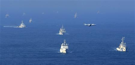 An aerial photo from Kyodo News shows Chinese ocean surveillance, fishery patrol ships and a Japan Coast Guard patrol ship (R and 2nd L) sailing about 27 km (17 miles) west from a group of disputed islands, known as Senkaku in Japan and Diaoyu in China, in the East China Sea in this September 18, 2012 file photograph taken by Kyodo. REUTERS/Kyodo/Files