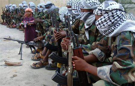 A boy carrying a toy gun stands near members of Somalia's hardline al Shabaab rebel group after attending Eid al-Adha prayers inside a football stadium north of the capital Mogadishu November 16, 2010. REUTERS/Feisal Omar
