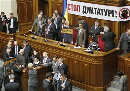 Opposition deputies block the speaker's rostrum to protest against an initiative to deprive Sergiy Vlasenko, their colleague and the lawyer of jailed former Prime Minister Yulia Tymoshenko, of the deputative powers and status during a session of the Ukrainian parliament in Kiev, March 5, 2013. REUTERS/Gleb Garanich