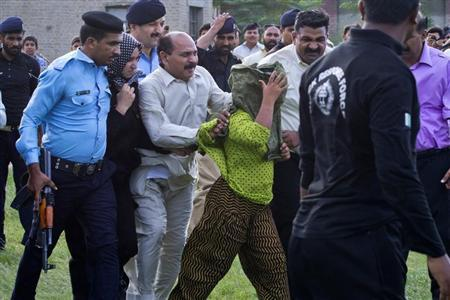 Security officials surrounding Rimsha Masih, (C, green scarf) a Christian girl accused of blasphemy, move her to a helicopter after her release from Adyala jail in Rawalpindi September 8, 2012. REUTERS/Stringer