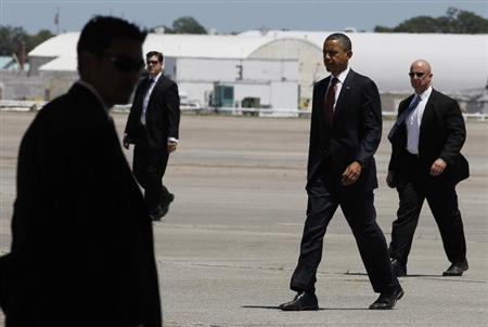 U.S. President Barack Obama walks with U.S. Secret Service agents as he prepares to board Air Force One at Hunter Army Airfield in Georgia before returning to Washington, April 27, 2012. REUTERS/Larry Downing