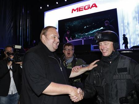 An actor in police costume greets Megaupload founder Kim Dotcom (L) as he launches his new file sharing site ''Mega'' in Auckland January 20, 2013. REUTERS/Nigel Marple/Files