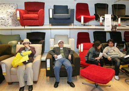Japanese shoppers sit on Swedish furniture retailer IKEA's sofas at the company's first store in Japan in Funabashi, east of Tokyo April 24, 2006. REUTERS/Yuriko Nakao/Files