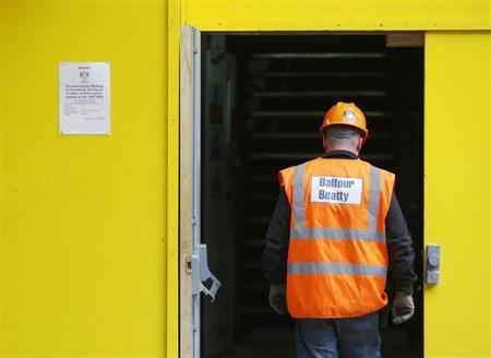A Balfour Beatty construction worker walks onto a site in London August 10, 2009. REUTERS/Luke MacGregor