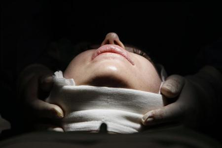 A woman lies on an operating table during a facelift surgery at a private plastic surgery clinic in Budapest, March 1, 2012. REUTERS/Bernadett Szabo
