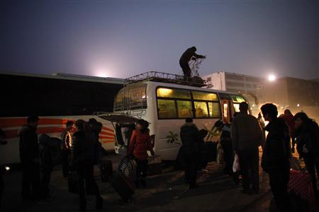 People arrive at a city bus station in the town of Zhoukou, Henan Province for a trip to work in a shoes factory at coastal industrial area of Jiangsu Province February 17, 2013. REUTERS/Carlos Barria