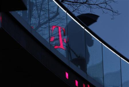 A man walks past the logo of Deutsche Telekom AG that is reflected on glass at their headquarters, in this file photo taken in Bonn December 5, 2012. REUTERS/Ina Fassbender/Files