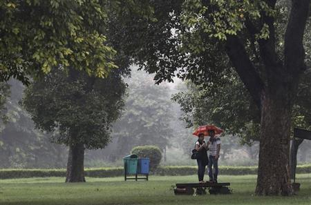 A couple stands under an umbrella on a platform in a park as it rains in New Delhi August 24, 2012. REUTERS/Adnan Abidi