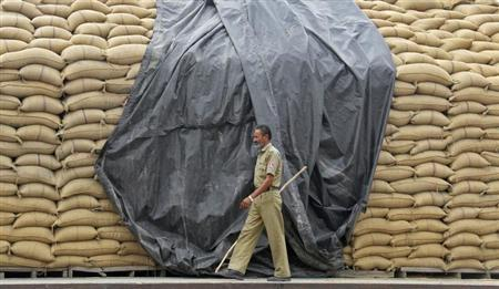 A security guard patrols besides stacked wheat sacks at a wholesale grain market in Chandigarh June 7, 2012. REUTERS/Ajay Verma/Files