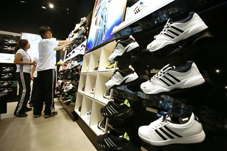 Staff arrange shoes at the new and world's largest Adidas Brand Center store in Beijing July 3, 2008. REUTERS/Claro Cortes IV/Files