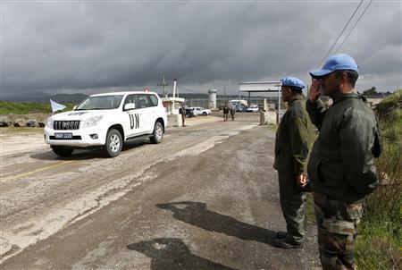 India's United Nations peacekeepers salute as a U.N. vehicle crosses from Syria into Israel at the Kuneitra border crossing on the Golan Heights March 5, 2013. REUTERS/Baz Ratner