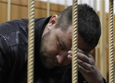 Yury Zarutsky sits in the defendant's holding cell during a court hearing in Moscow March 7, 2013. REUTERS/Maxim Shemetov