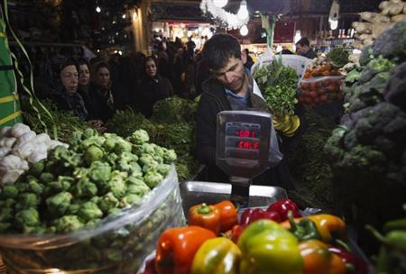 EDITORS' NOTE: Reuters and other foreign media are subject to Iranian restrictions on leaving the office to report, film or take pictures in Tehran. A shopkeeper checks the prices of vegetables for a customer at a bazaar in northern Tehran February 29, 2012. REUTERS/Morteza Nikoubazl