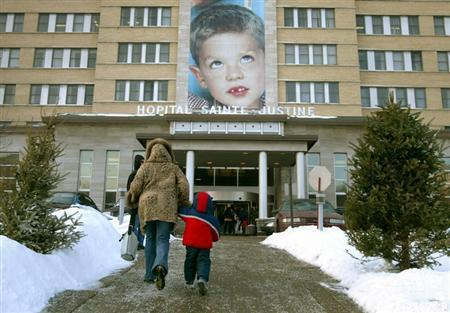 A mother and child walk into Sainte-Justine Hospital in Montreal January 22, 2004. REUTERS/Shaun Best