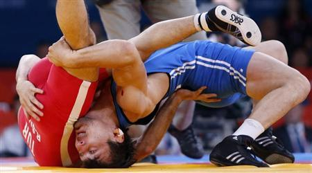 Kazakhstan's Akzhurek Tanatarov (in blue) fights with Turkey's Ramazan Sahin for the bronze medal of the Men's 66Kg Freestyle wrestling at the ExCel venue during the London 2012 Olympic Games August 12, 2012. REUTERS/Suhaib Salem