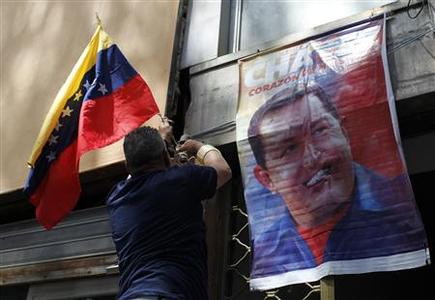 A Caracas resident puts up the national flag next to a poster of Venezuela's late President Hugo Chavez, in Caracas, March 7, 2013. REUTERS/Carlos Garcia Rawlins