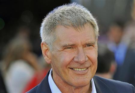 U.S. actor Harrison Ford poses for photographs as he arrives for the British premiere of ''Cowboys and Aliens'' at the O2 Arena in London August 11, 2011. REUTERS/Toby Melville