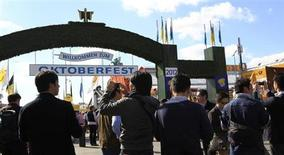 Chinese tourists take pictures of the Oktoberfest entrance during their visit of the famous Oktoberfest in Munich September 28, 2012. REUTERS/Michaela Rehle