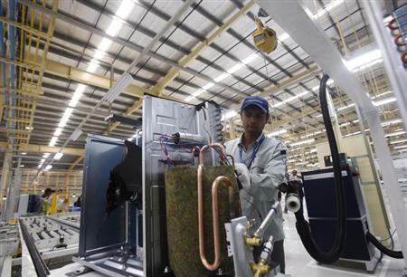 An employee works at an air conditioner production line during a media tour at Panasonic's newly launched ''eco ideas'' factory at Jhajjar district in Haryana December 12, 2012. REUTERS/Mansi/Files