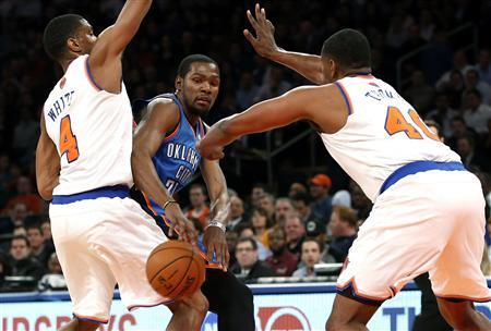 Oklahoma City Thunder forward Kevin Durant (C) passes between New York Knicks' Kurt Thomas (R) and James White during the first quarter of their NBA basketball game in New York, March 7, 2013. REUTERS/Mike Segar