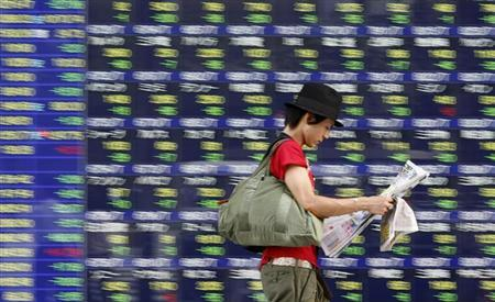 A man reading a newspaper, walks past a stock quotation board outside a brokerage in Tokyo September 14, 2009. REUTERS/Toru Hanai/Files