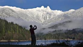 A visitor to Capilano Park takes pictures of the pointed peaks of The Lions covered in snow in North Vancouver, British Columbia, in this December 14, 2012 file photograph. REUTERS/Andy Clark/Files