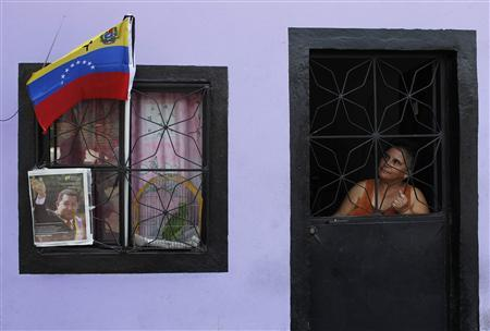A woman looks out of her door at a flag and portrait of Venezuela's late President Hugo Chavez in Caracas, March 7, 2013. REUTERS/Carlos Garcia Rawlins