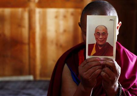 A monk holds a picture of Tibetan spiritual leader Dalai Lama inside of his room ahead of the Tibetan New Year which starts on Wednesday at Labrang Monastery in Xiahe county, Gansu Province February 21, 2012. REUTERS/Carlos Barria/Files