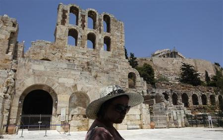 A tourist stands in front of the ancient Herodes Atticus theatre below the hill of the Acropolis in Athens July 16, 2012. REUTERS/John Kolesidis