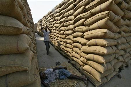 A labourer rests next to stacked sacks of paddy crop at a wholesale grain market in Chandigarh October 15, 2012. REUTERS/Ajay Verma/Files