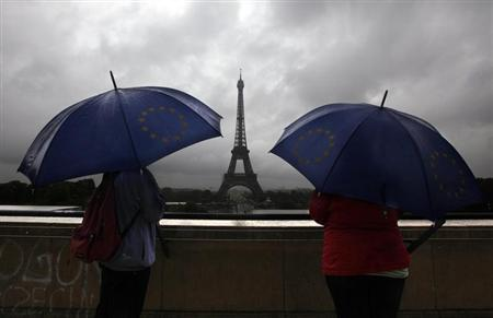 Tourists protect themselves from the rain under umbrellas in front of the Eiffel tower as they visit the French capital during summer holidays in Paris July 19, 2011. REUTERS/Eric Gaillard