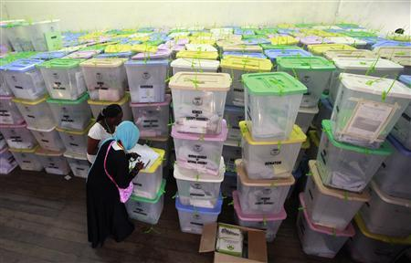 Polling clerks record information on a pile of ballot boxes containing cast ballot papers at the Chandaria tallying centre in Kenya's coastal city of Mombasa March 6, 2013. REUTERS/Joseph Okanga