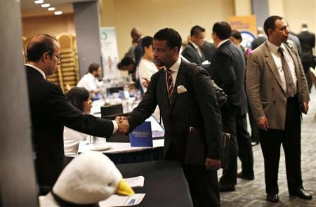 A job seeker (R) meets with a prospective employer at a career fair in New York City, October 24, 2012. REUTERS/Mike Segar