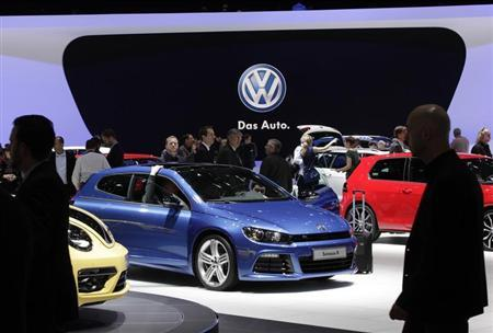 Visitors stroll through cars on the Volkswagen booth during the second media day of the 83rd Geneva Car Show at the Palexpo Arena in Geneva March 6, 2013. REUTERS/Denis Balibouse