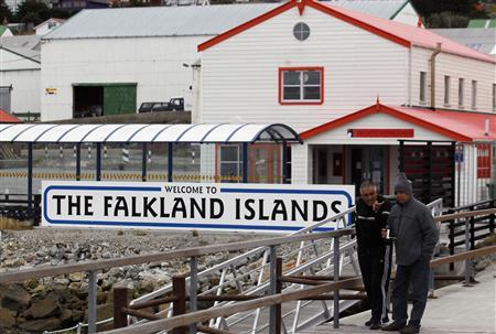 Argentine Falklands War veterans Hugo Romero (R) and Walter Sarverry walk next to a ''Welcome to the Falkland Islands'' sign in Port Stanley, in this picture taken March 14, 2012. REUTERS/Marcos Brindicci