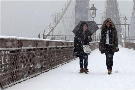 Women walk on the Brooklyn Bridge during a snowstorm in New York, March 8, 2013. A slow moving winter storm brought a combination of snow, rain and high winds to the northeast U.S. Friday after moving through the mid-Atlantic states earlier in the week. REUTERS/Eduardo Munoz