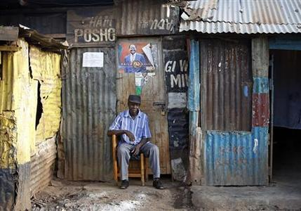 A supporter of Kenyan Prime Minister Raila Odinga sits in front of a poster outside his house as he waits for election results in the Kibera slum in Nairobi March 8, 2013. Kenya said it was determined to complete the count on Friday in a tight presidential race that has put Uhuru Kenyatta ahead of his main rival Prime Minister Raila Odinga and in with a chance of outright victory. REUTERS/Goran Tomasevic