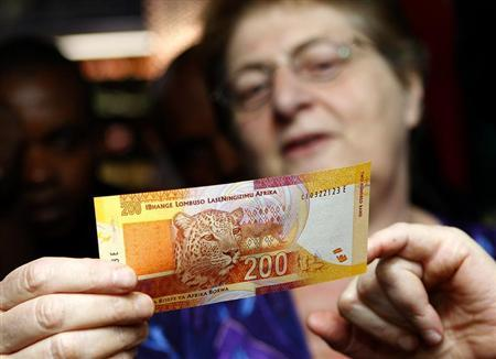 South African Reserve Bank Governor Gill Marcus shows off a new South African banknote, which features an image of former president Nelson Mandela on the front and images of the country's ''Big Five'' wild animals on the reverse, before conducting the first transaction in Pretoria, November 6, 2012. REUTERS/Siphiwe Sibeko