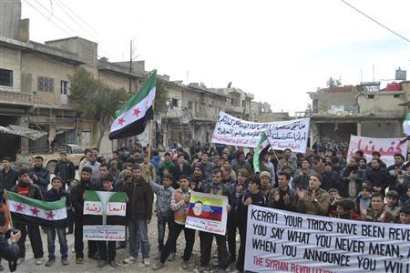 Demonstrators carry banners and wave Syrian opposition flags during a protest against Syria's President Bashar al-Assad in Kafranbel, near Idlib, March 8, 2013. REUTERS/Raed Al-Fares/Shaam News Network/Handout