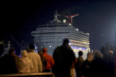 The Carnival Triumph cruise ship is towed towards the dock as spectators watch at the port of Mobile, Alabama, February 14, 2013. REUTERS/ Lyle Ratliff