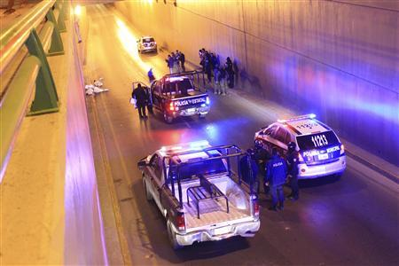 WARNING: THE FOLLOWING IMAGE CONTAINS GRAPHIC CONTENT Police and forensic technicians stand near the wrapped bodies of two dead people hanging from an overpass as three more dead bodies lie on the ground in Saltillo March 8, 2013. REUTERS/Stringer