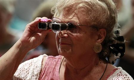A senior citizen at West Palm Beach Century Village uses binoculars to watch U.S. President Barack Obama during a campaign event in Florida July 19, 2012. REUTERS/Kevin Lamarque