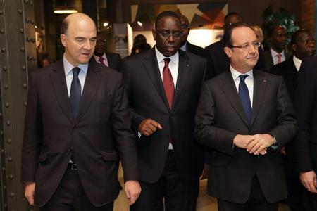 French President Francois Hollande (R), his Senegalese counterpart Macky Sall and Finance Minister Pierre Moscovici (L) arrive at the International Solidarity and Development meeting in Paris, March 1, 2013. REUTERS/Philippe Wojazer