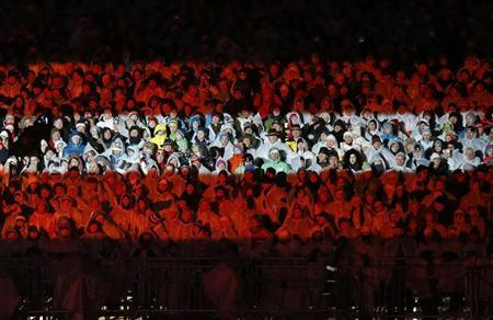 Spectators are illuminated with the colours of the Austrian flag during the opening ceremony of the World Alpine Skiing Championships in Schladming February 4, 2013. REUTERS/Leonhard Foeger