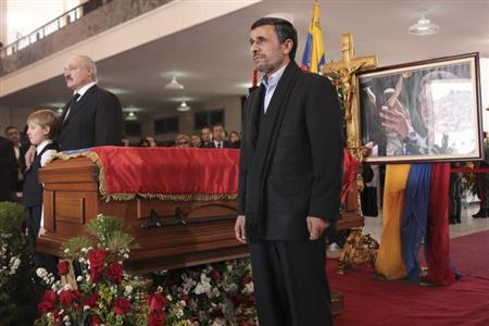 Iran's President Mahmoud Ahmadinejad stands next to the coffin of Venezuela's late President Hugo Chavez, during the funeral service at the Military Academy in Caracas March 8, 2013, in this picture provided by the Miraflores Palace. REUTERS/Miraflores